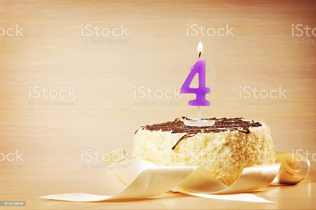 Birthday cake with burning candle as a number four stock photo