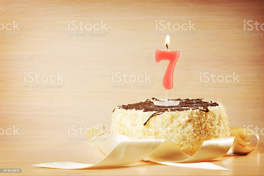 Birthday cake with burning candle as a number seven stock photo