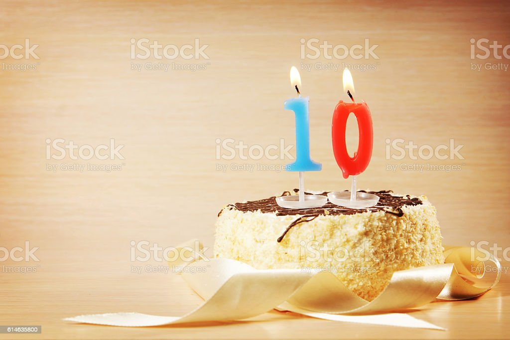 Birthday cake with burning candle as a number ten stock photo