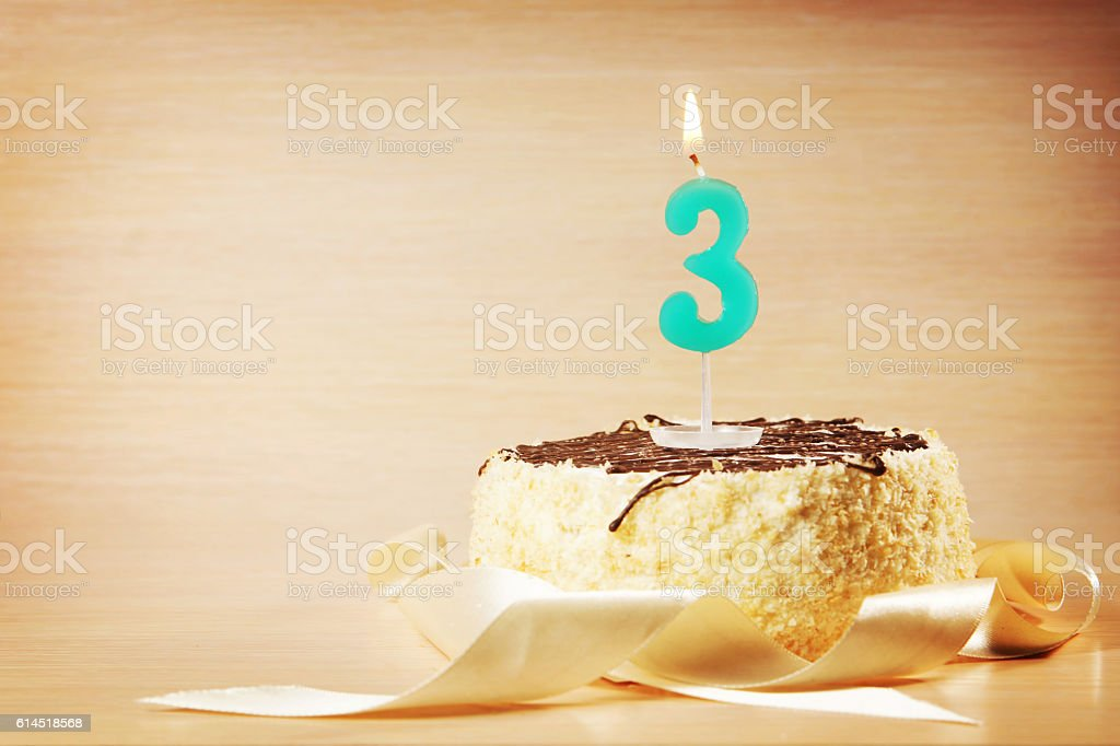 Birthday cake with burning candle as a number three stock photo
