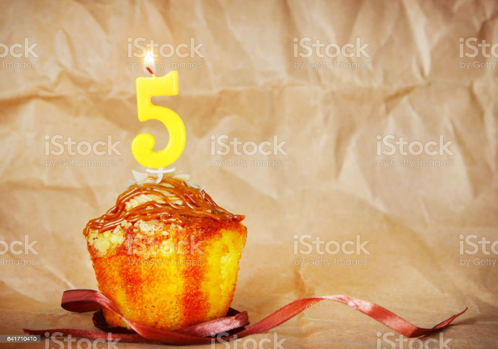 Birthday cake with burning candle as number five stock photo
