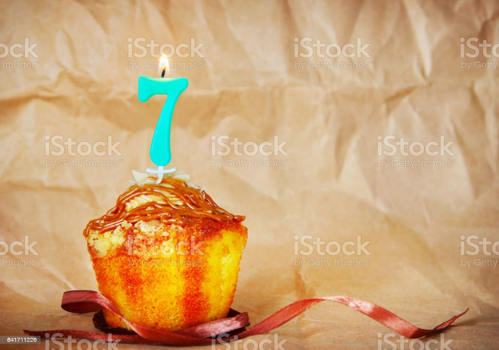 Birthday cake with burning candle as number seven stock photo