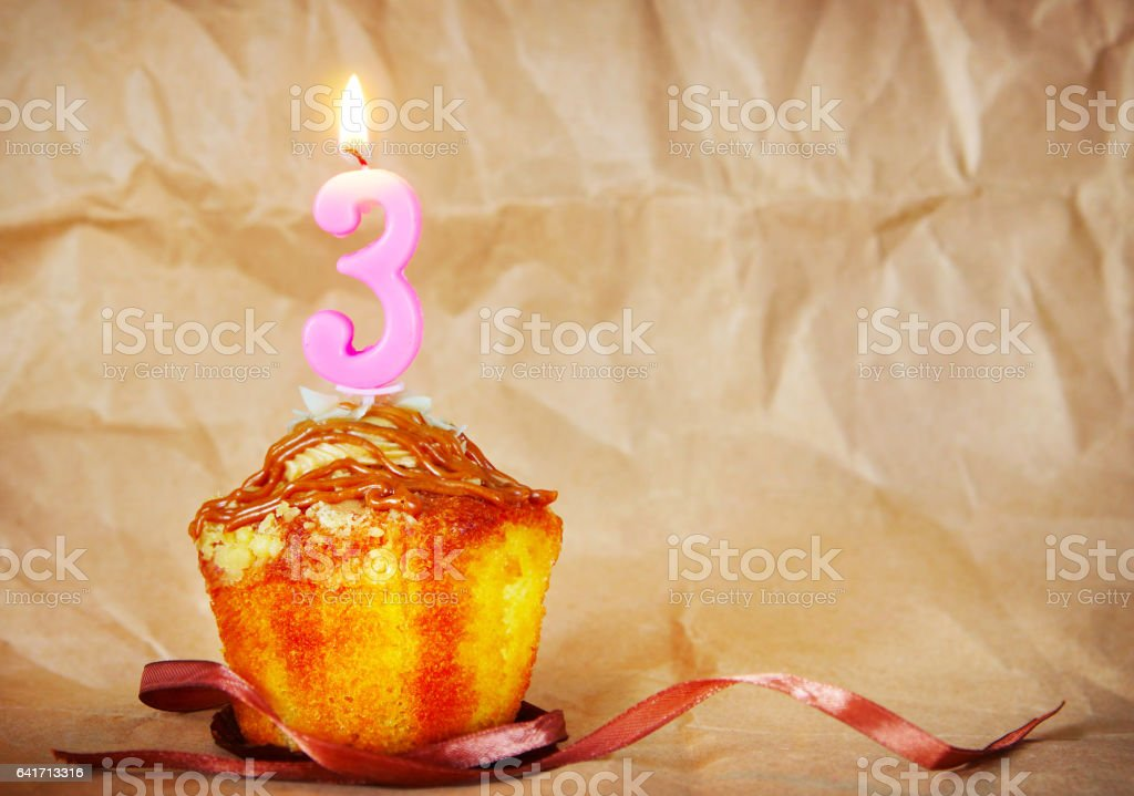Birthday cake with burning candle as number three stock photo