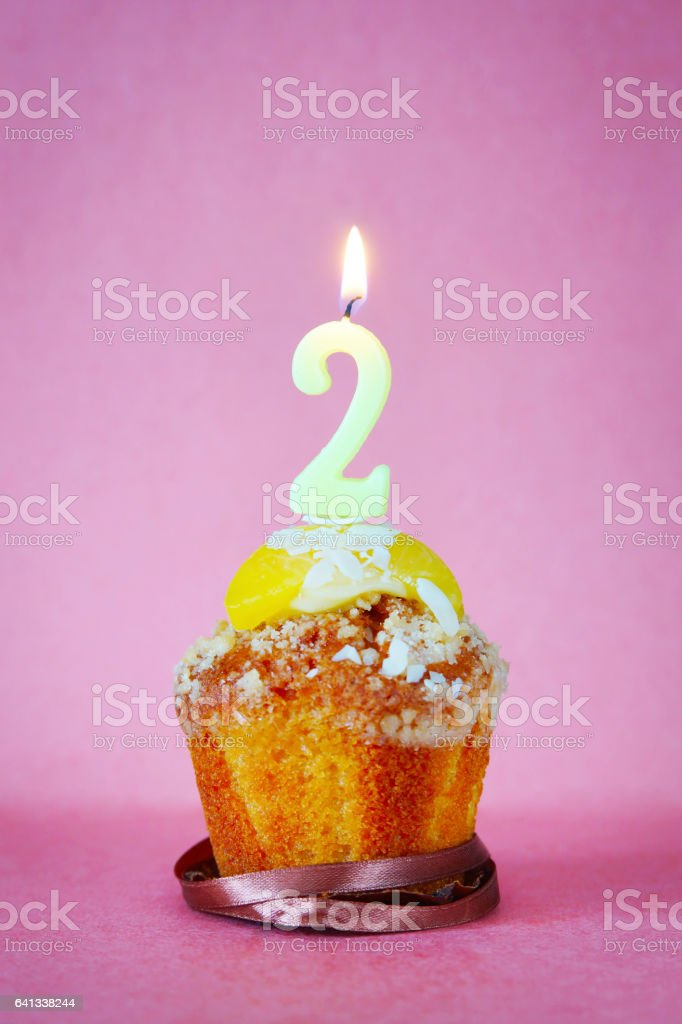 Birthday cake with burning candle as number two stock photo