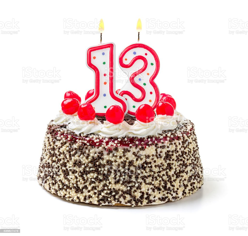 Birthday cake with burning candle number 13 stock photo