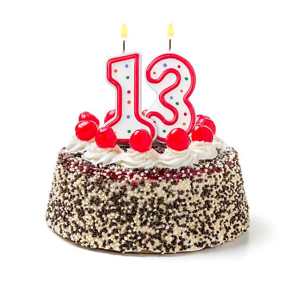 Birthday cake with burning candle number 13 stock photo