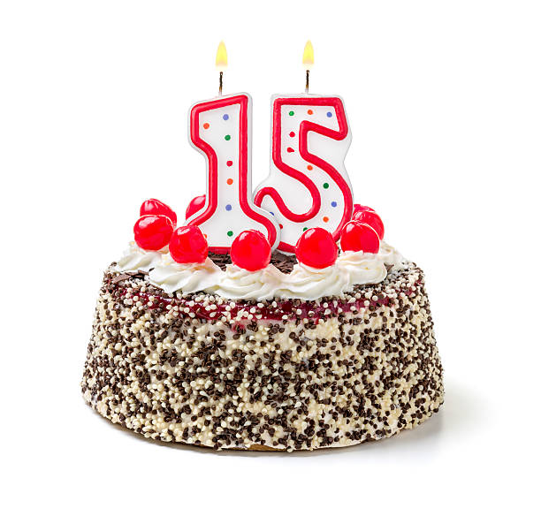 Birthday cake with burning candle number 15 stock photo