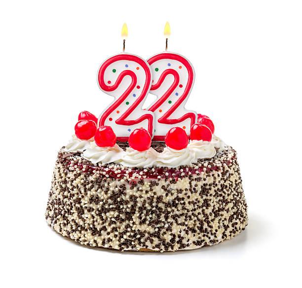 Birthday cake with burning candle number 22 stock photo