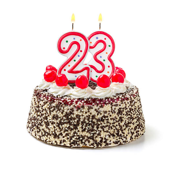 Birthday cake with burning candle number 23 stock photo