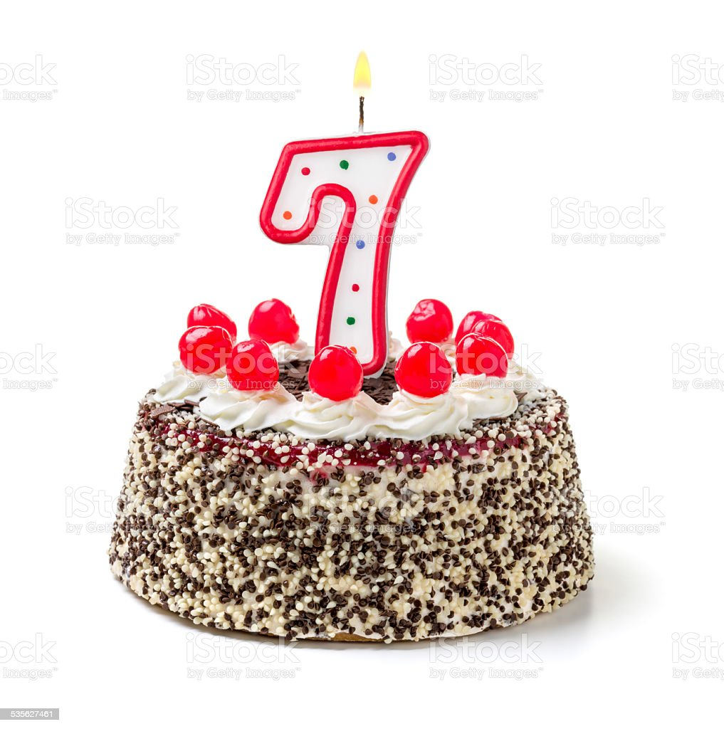 Birthday cake with burning candle number 7 stock photo