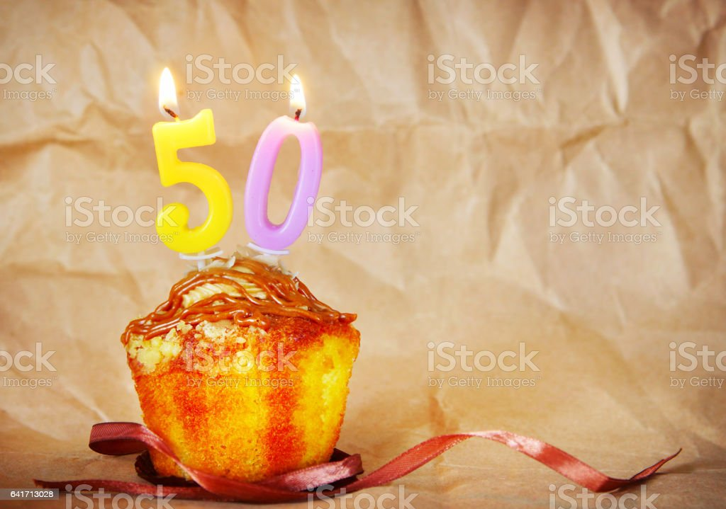 Birthday cake with burning candles as number fifty stock photo