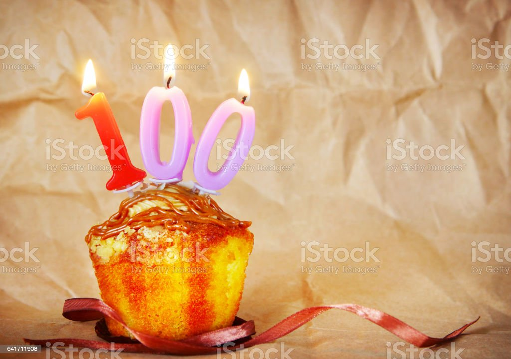 Birthday cake with burning candles as number one hundred stock photo