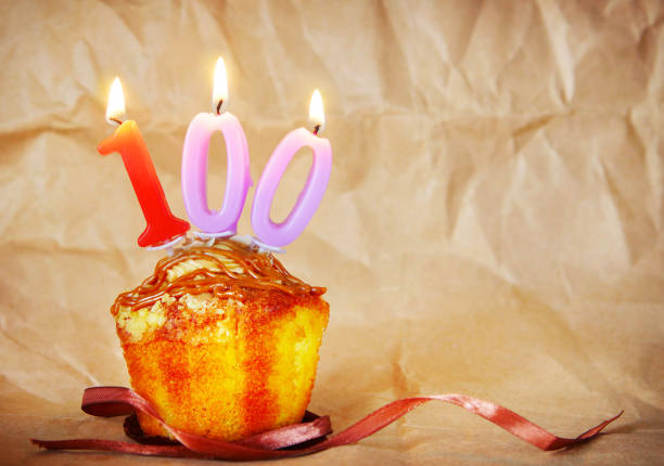 Birthday cake with burning candles as number one hundred Birthday cake with burning candles as number one hundred on brown paper background 100th anniversary stock pictures, royalty-free photos & images