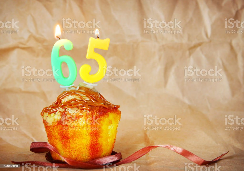Birthday cake with burning candles as number sixty five stock photo
