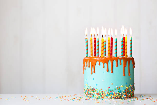 Birthday cake with candles and drip icing Colorful birthday cake with lots of candles and orange drip icing birthday cake stock pictures, royalty-free photos & images
