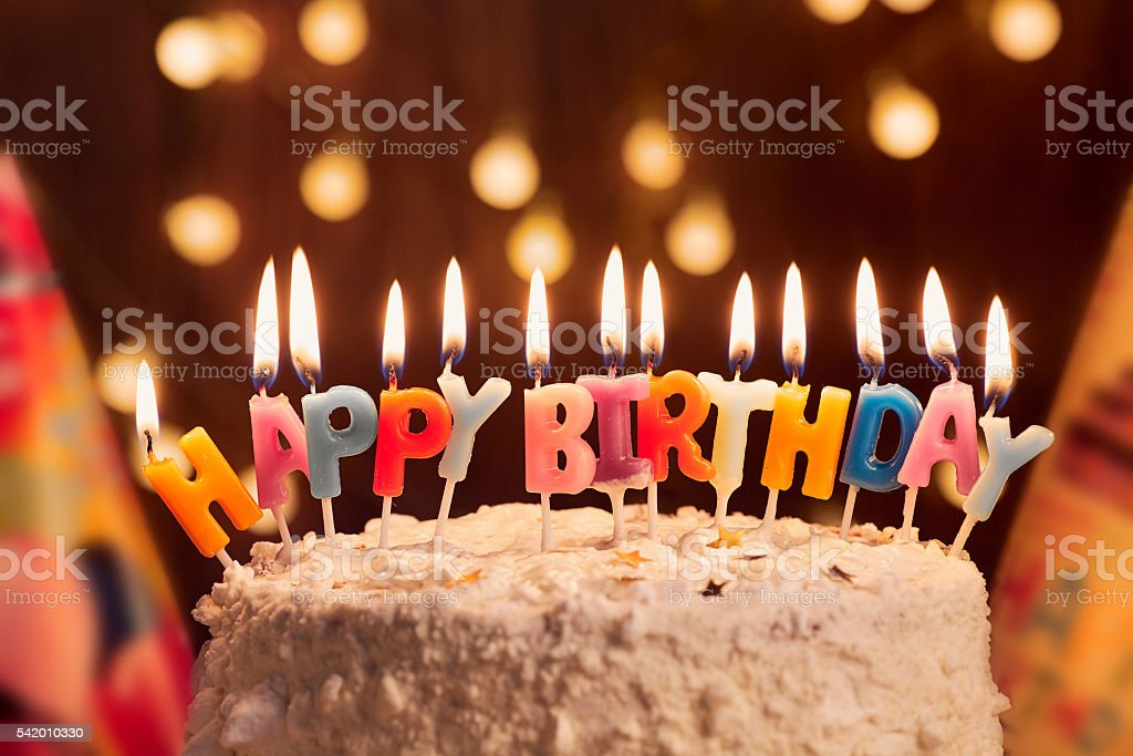 Birthday cake with candles, bright lights bokeh.Celebration. stock photo