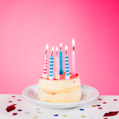 Birthday cake with candles standing on the table, isolated on pink background, square composition, copy space.