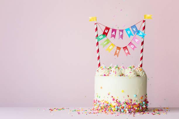 De cake van de verjaardag met kleurrijke gelukkige verjaardagsbanner foto