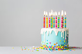 istock Birthday cake with drip icing and colorful candles 1253501415
