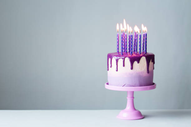 Birthday cake with drip icing and purple candles Birthday cake with drip icing and lots of purple candles against a gray background cakestand stock pictures, royalty-free photos & images