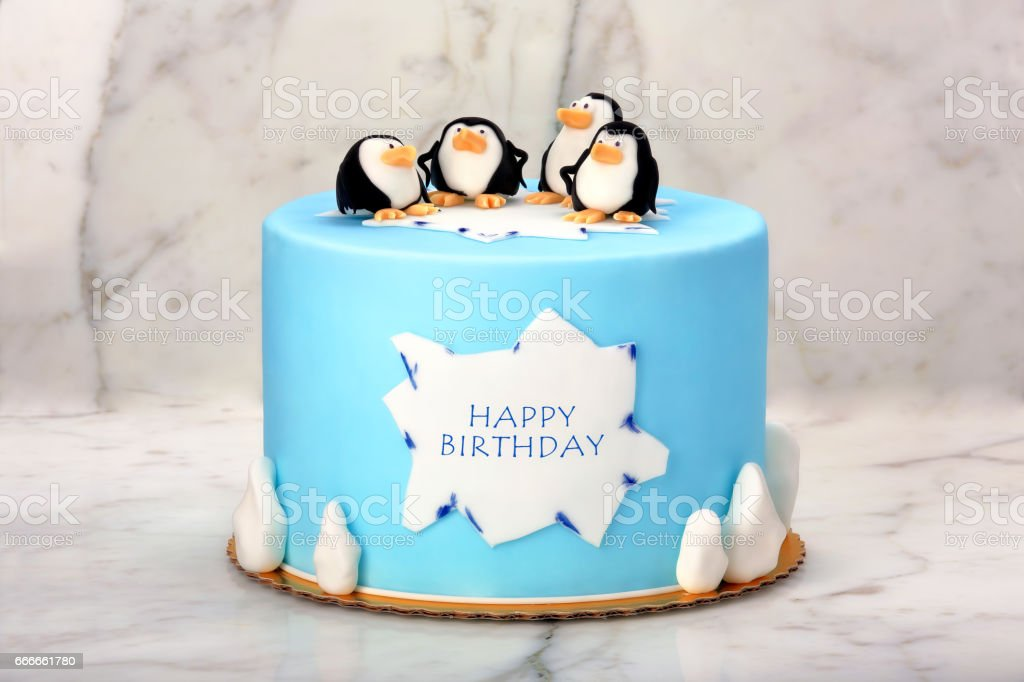 Birthday cake with penguins on the stone background stock photo