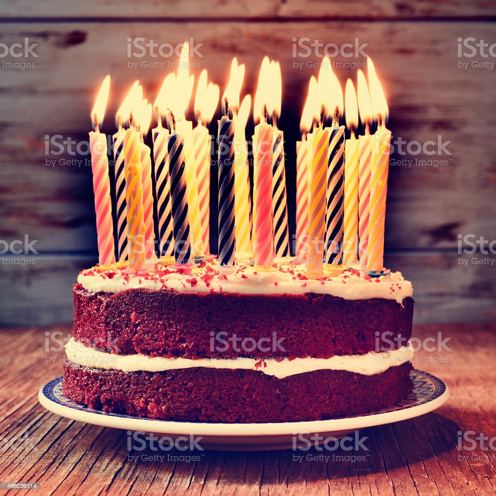 birthday cake with some lit candles, filtered stock photo
