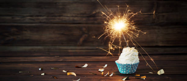 birthday cake with sparkler on old wooden background stock photo