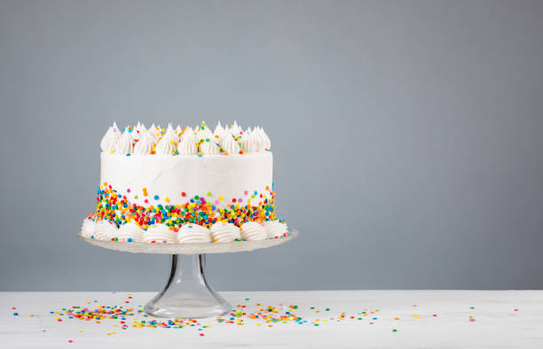 Birthday Cake with Sprinkles White Birthday cake with colorful Sprinkles over a neutral gray background. cake stock pictures, royalty-free photos & images