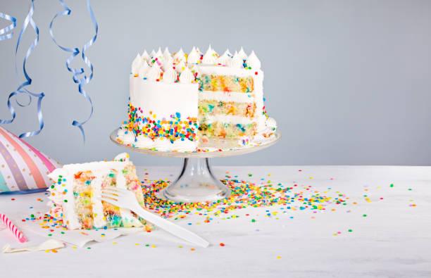 birthday cake with sprinkles - кусок торта стоковые фото и изображения