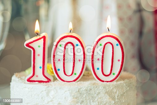 istock Birthday candle as number one hundred on top of sweet cake on the table, 100th birthday 1306493881