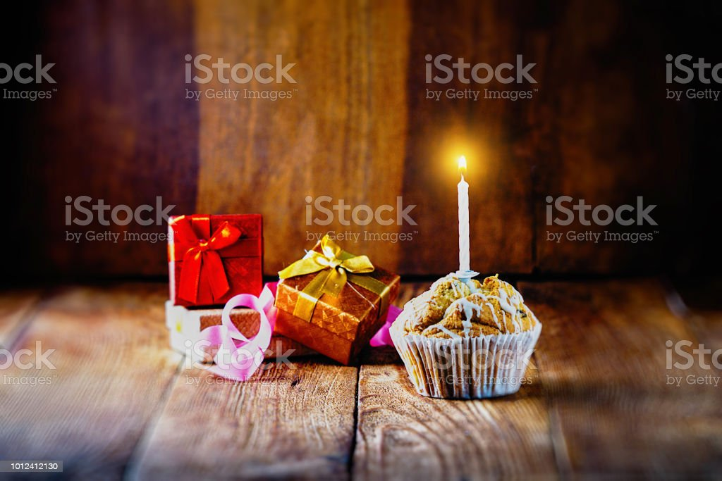 Birthday card. Cupcake with a candle and gift boxes on a wooden...