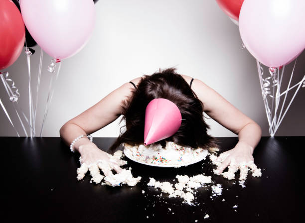 Birthday Celebrations Portrait of a young woman laying head first into her birthday cake. spaghetti straps stock pictures, royalty-free photos & images