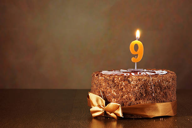 Birthday chocolate cake with burning candle as a number nine stock photo