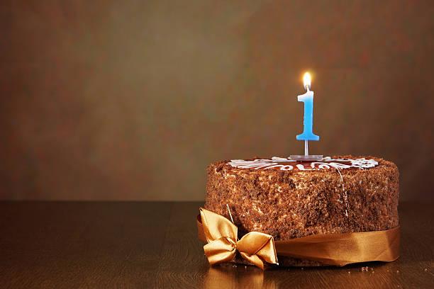 geburtstag schokoladenkuchen mit brennenden kerze als eine nummer ein - nummer 1 kuchen stock-fotos und bilder