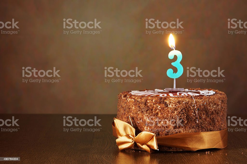Birthday chocolate cake with burning candle as a number three stock photo