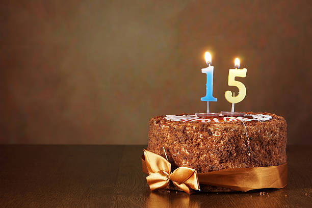 Birthday chocolate cake with burning candles as a number fifteen stock photo