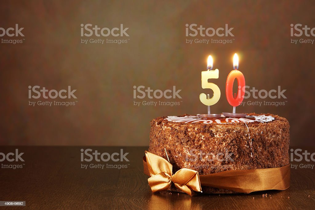 Birthday chocolate cake with burning candles as a number fifty stock photo
