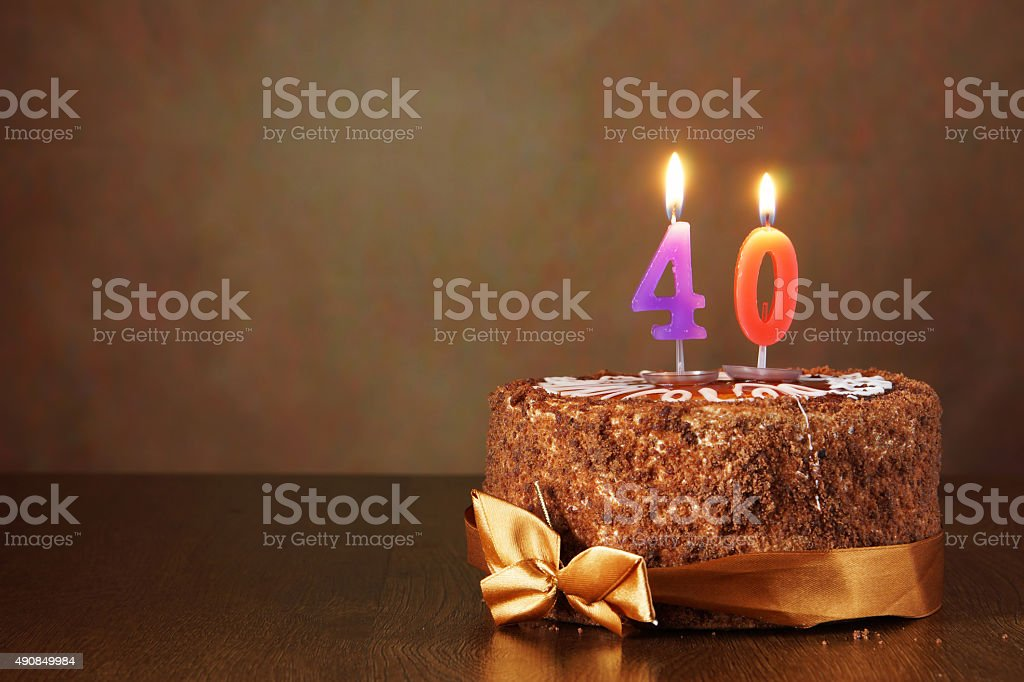 Birthday chocolate cake with burning candles as a number forty stock photo