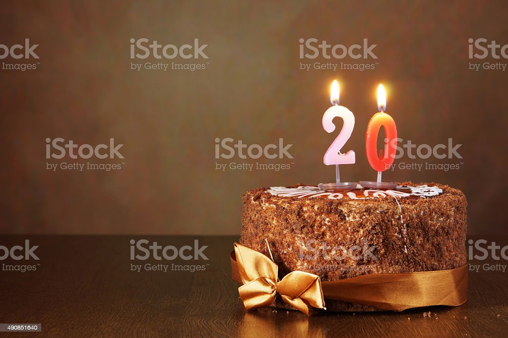 Birthday chocolate cake with burning candles as a number twenty stock photo