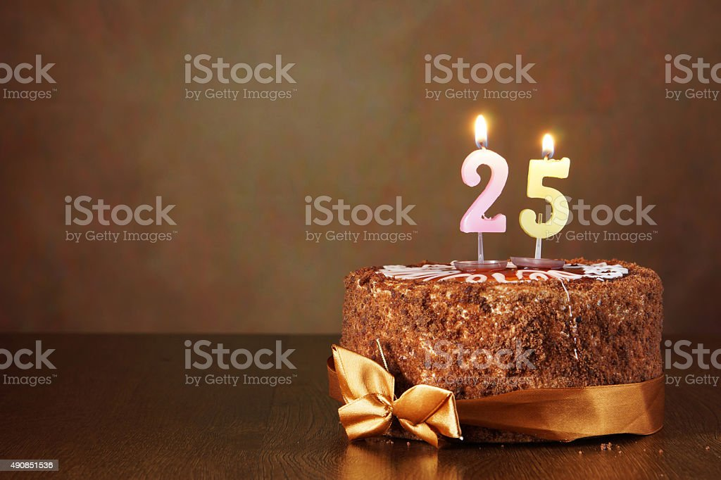 Birthday chocolate cake with burning candles as number twenty five stock photo