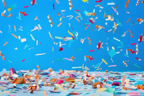 verjaardag confetti op blauwe achtergrond - confetti stockfoto's en -beelden