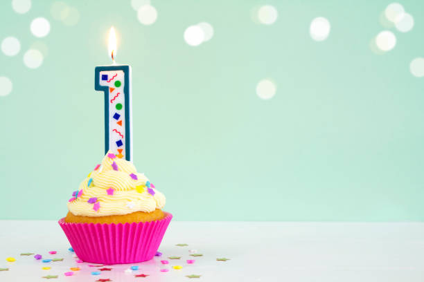 Birthday Cupcake Vanilla buttercream cupcake with birthday candle, on a green background. first birthday stock pictures, royalty-free photos & images