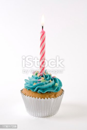 A pink birthday candle lit on a cupcake with blue icing and multi-colored stars.