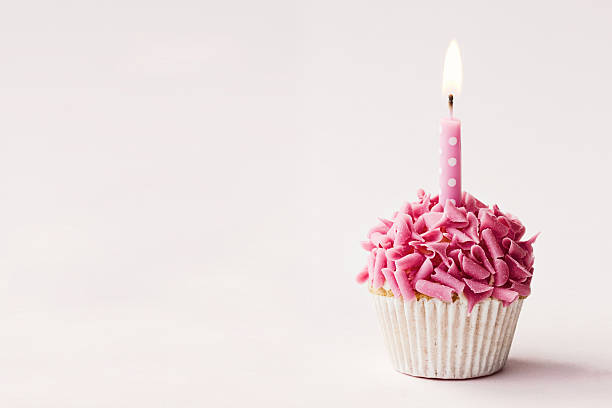 Birthday cupcake Cupcake decorated with pink chocolate curls and a single candle birthday candle stock pictures, royalty-free photos & images