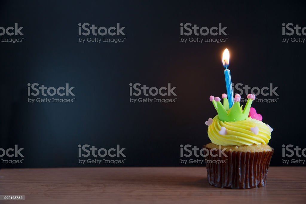 Birthday cupcake with a single blue candle.Cupcake with yellow cream and heart for love valentines. stock photo
