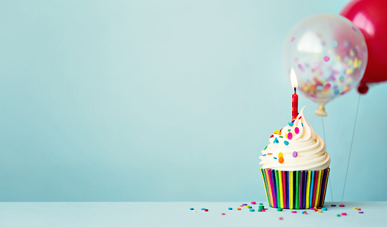 Birthday cupcake with colorful balloons and confetti