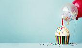 istock Birthday cupcake with balloons 1250275937
