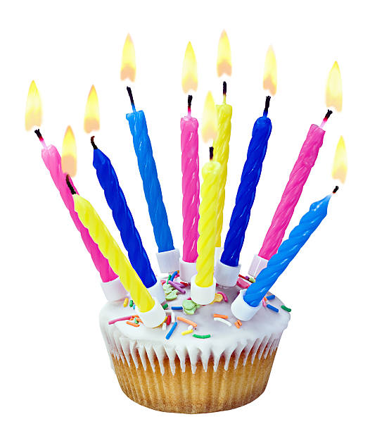 Birthday cupcake with burning candles stock photo