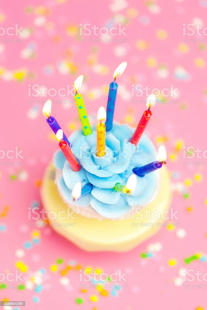 Birthday Cupcake with candles on Pink Background with Confetti Sprinkles stock photo