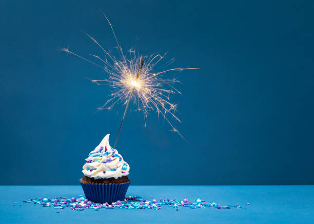 Birthday Cupcake with sparkler Birthday Cupcake with sparkler against a blue background. cupcake stock pictures, royalty-free photos & images